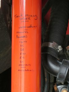 handwritten note on sprayer as reminder for filling sequence