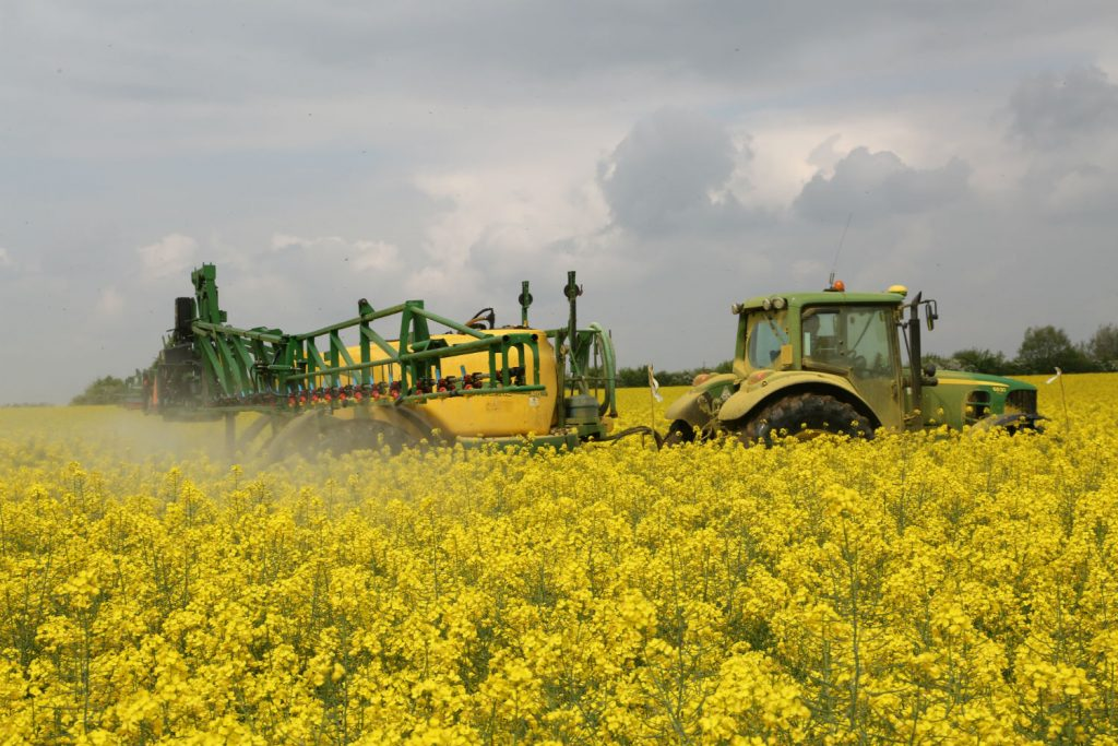 Tractor and sprayer over oilseed rape applying pesticides